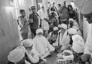 Keertan (hymn singing) for Nelson Mandela's health and wellbeing in the corridor outside his former prison cell (Robben Island off Cape Town Coast). Onlookers were heartened to see people of the Sikh Dharam praying for the good health of 'Madiba'. Dec 2012