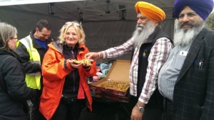 Guru Nanak Gurdwara Smethwick President Malkit Singh, distributes pizza and chips Langar to all volunteers
